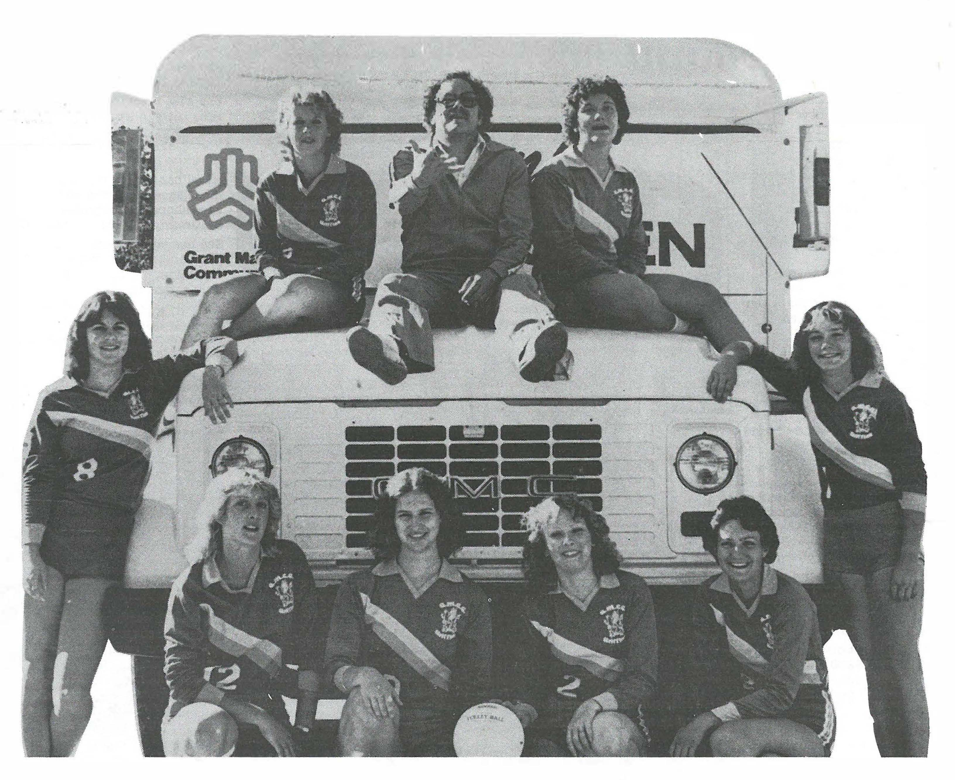 Photograph of the women's volleyball team from 1981 and their coach sitting on top of and around a bus.